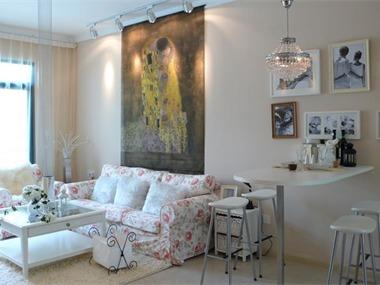 客厅光线不好,背景墙选用高光饰面板上墙的方式,壁挂